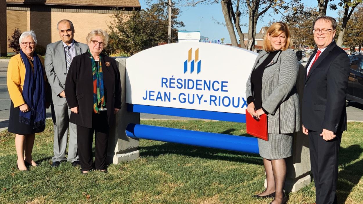 Les cinq personnes encadrent l'enseigne de la Résidence Jean-Guy-Rioux