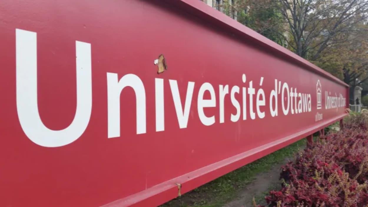 Un panneau rouge sur lequel est inscrit le nom d'une université.