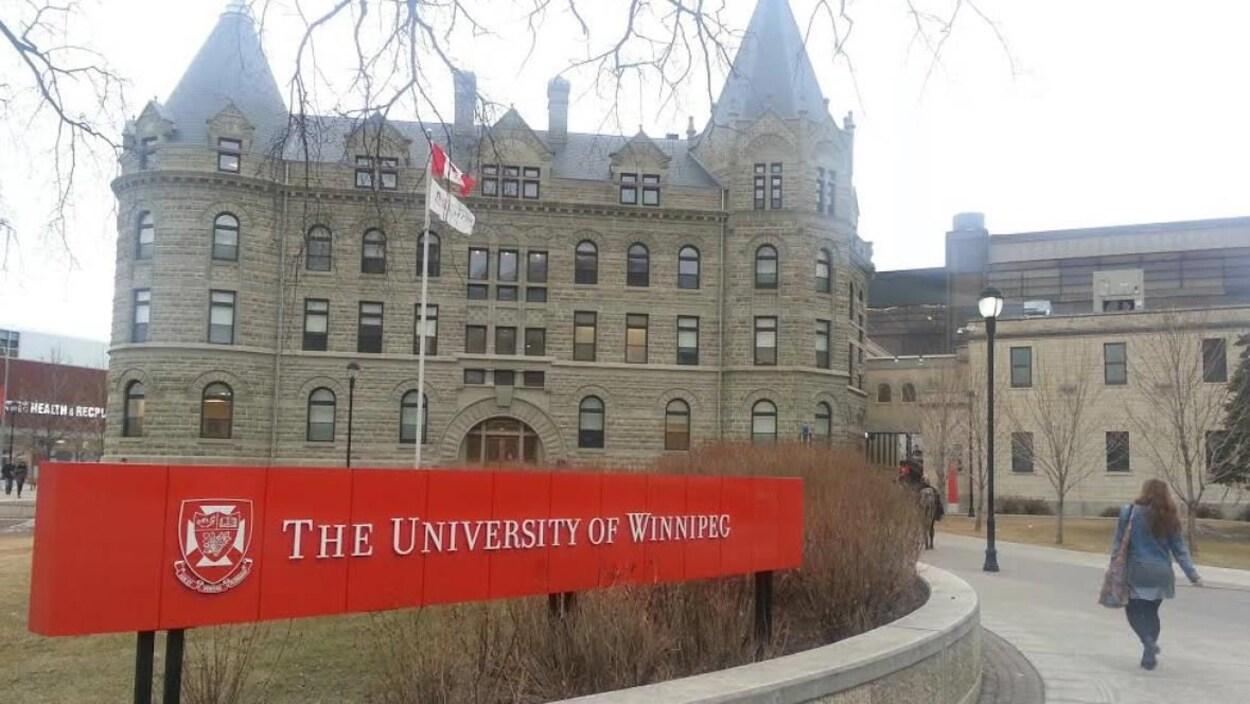 Une femme marche devant le bâtiment principal de l'Université de Winnipeg sur l'avenue Portage.