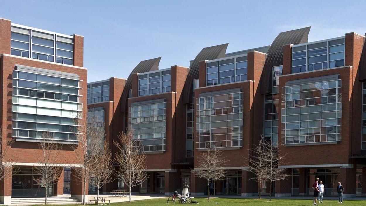 Un édifice avec des étudiants sur la pelouse.