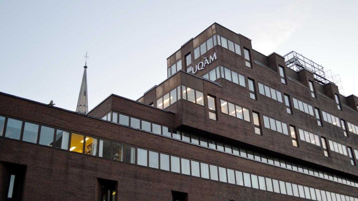 Une photographie montrant l'un des bâtiments de l'Université du Québec à Montréal (UQAM), dont quelques lumières sont allumées à l'intérieur.