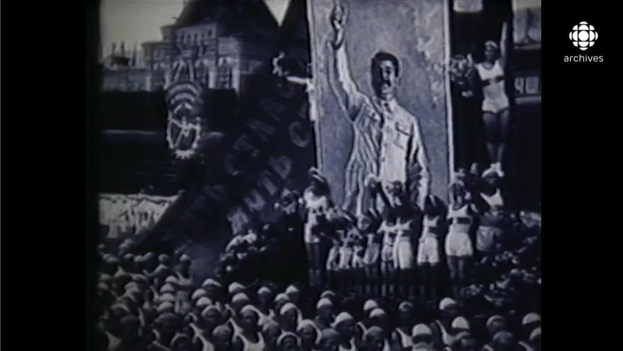 Char allégorique avec une affiche géante de Staline au milieu d'une parade avec des femmes costumées en paysannes