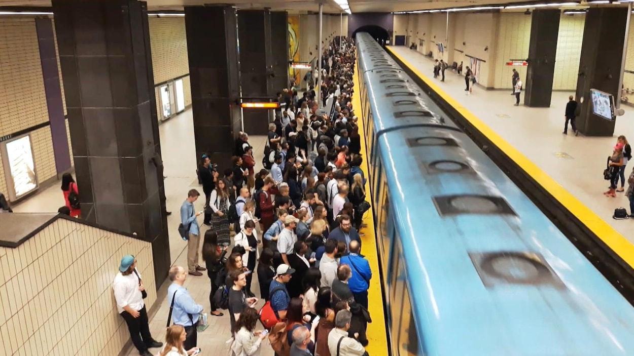 Des usagers sur un quai du métro de Montréal, alors que le train arrive en station.