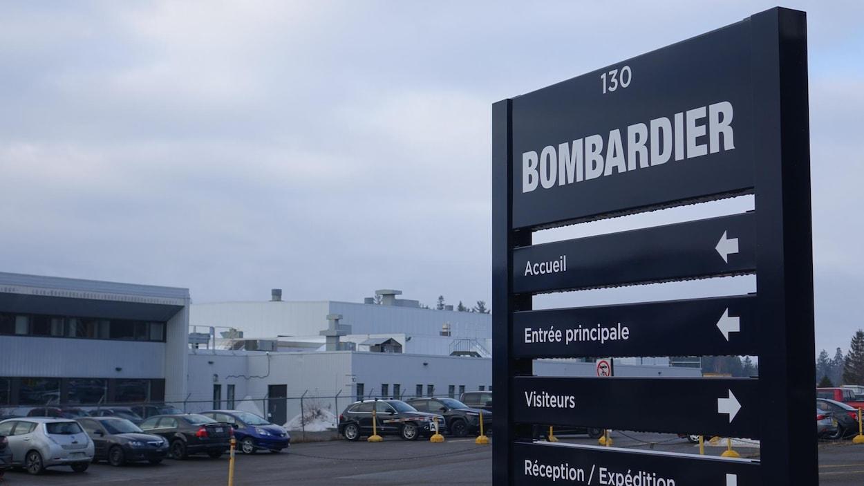 Pancarte à l'entrée de l'usine Bombardier de La Pocatière, stationnement, usine à l'arrière.