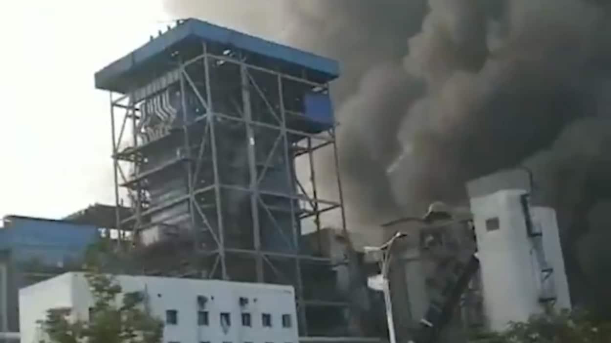 Un énorme nuage de fumée grise surplombe l'usine.