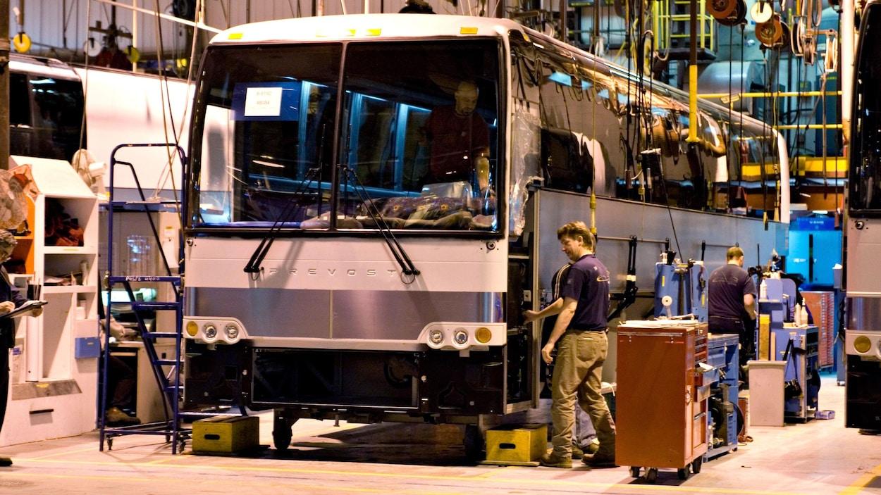 Des employés travaillent au montage d'un autobus Prévost à l'intérieur d'une usine.