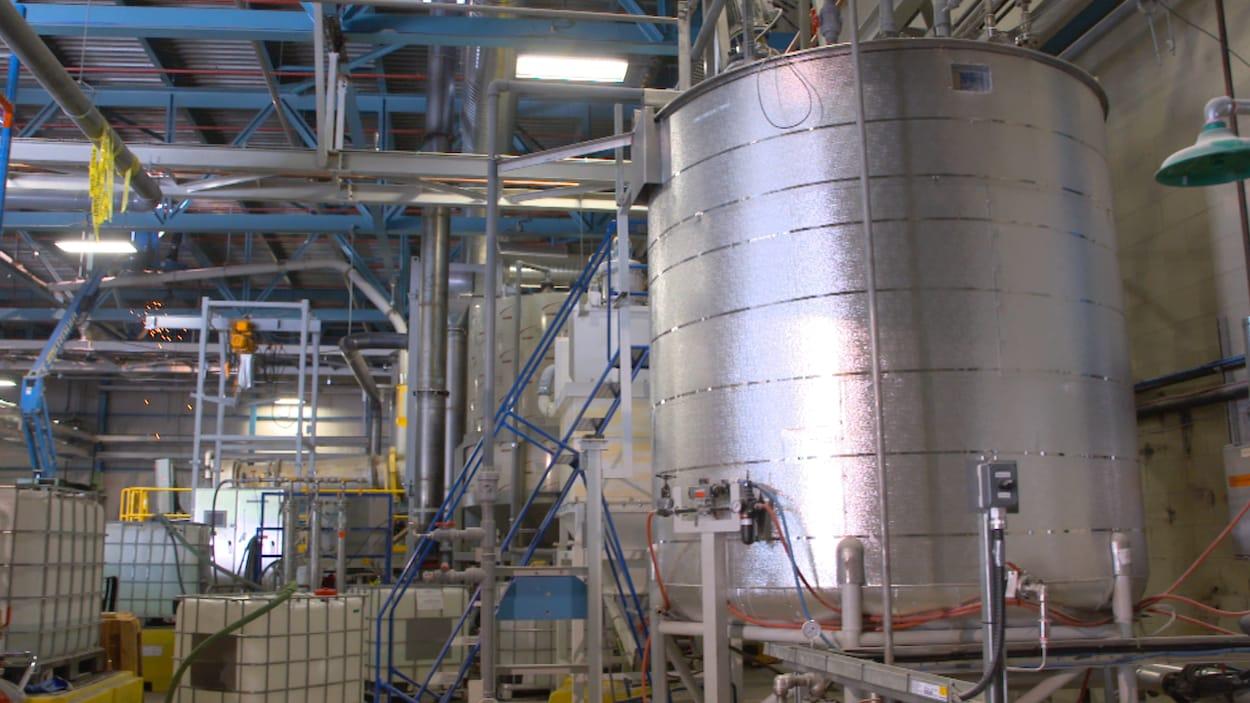On voit une grande cuve industrielle métallique, située à l'intérieur de l'usine. À l'arrière-plan, on voit des tuyaux et des conduits métalliques.