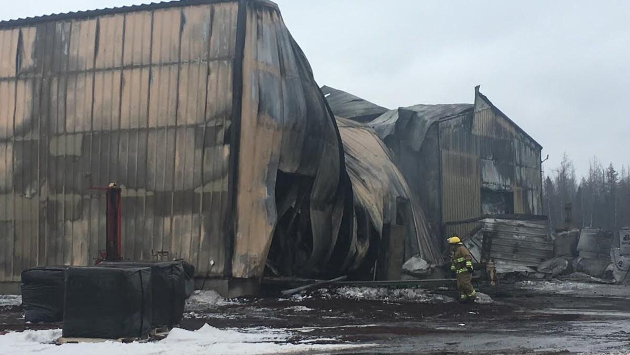 Un pompier examine la structure déformée par la chaleur