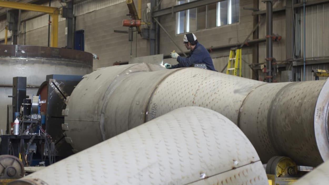 Un travailleur parmi des composantes d'oléoduc.