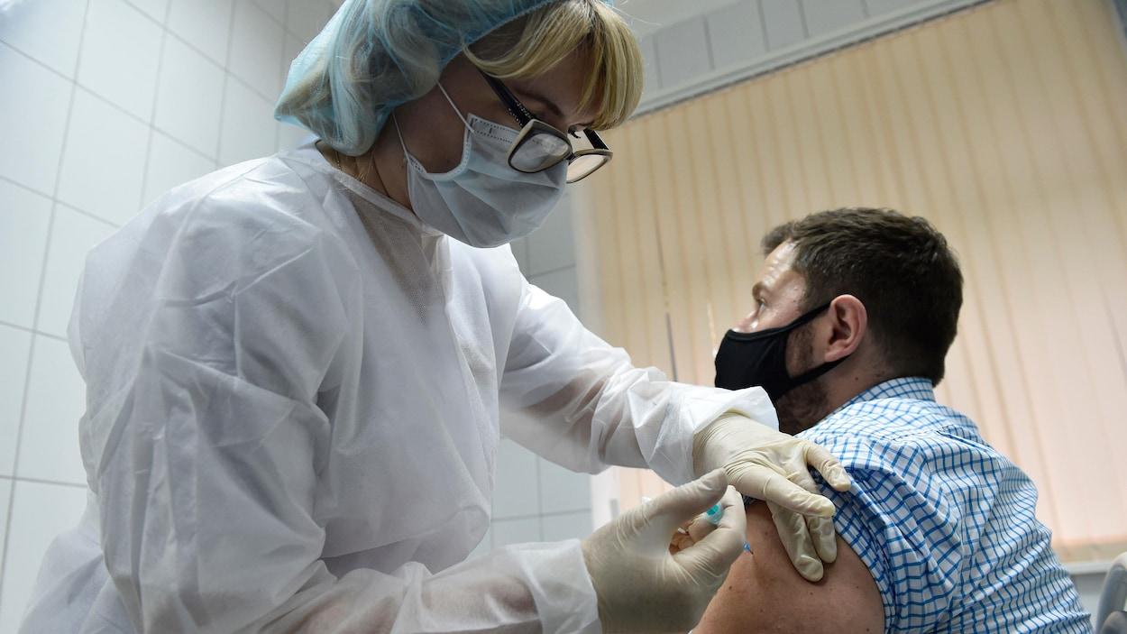 Une infirmière russe vaccine un homme.