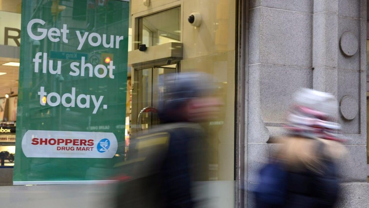 Une affiche dans une vitrine de pharmacie annonçant la disponibilité du vaccin contre la grippe, des gens marchent devant.