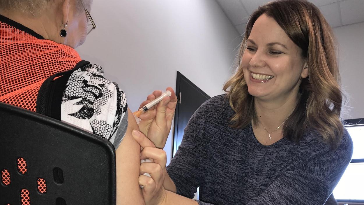 Une dame donne un vaccin à une autre dame, qu'on voit de dos.
