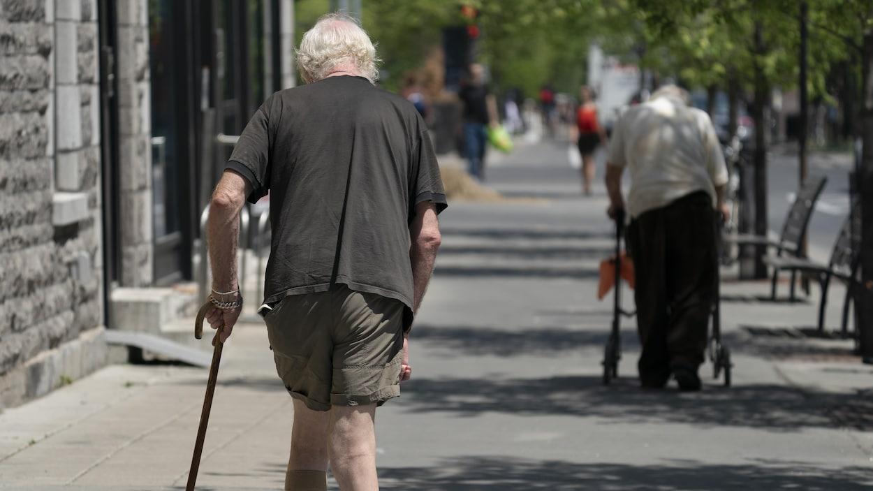 Des aînés marchent sur un trottoir.