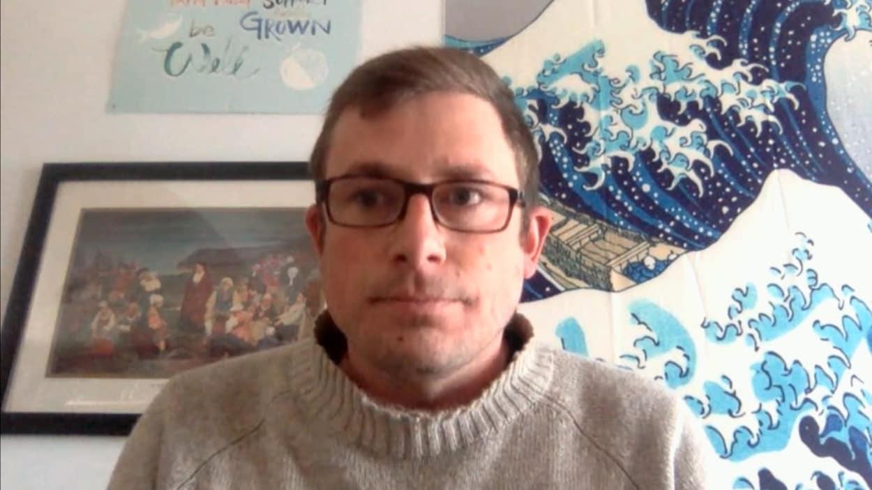 Une image d'un homme avec des lunette, avec une toile d'ocean derrière lui et un tableau de la déportation des acadiens.