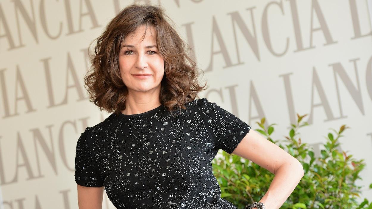 L'actrice et réalisatrice française Valérie Lemercier est assise sur un siège en osier blanc, la main gauche dans son pantalon.