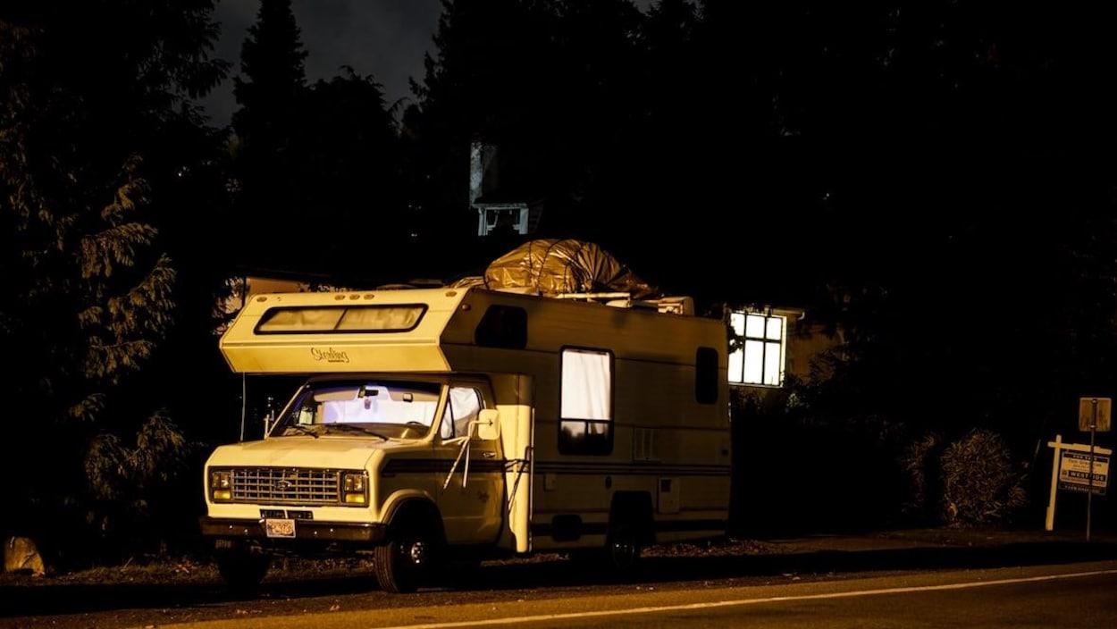 Un véhicule récréatif stationné en pleine nuit dans un rue résidentielle du Grand Vancouver.