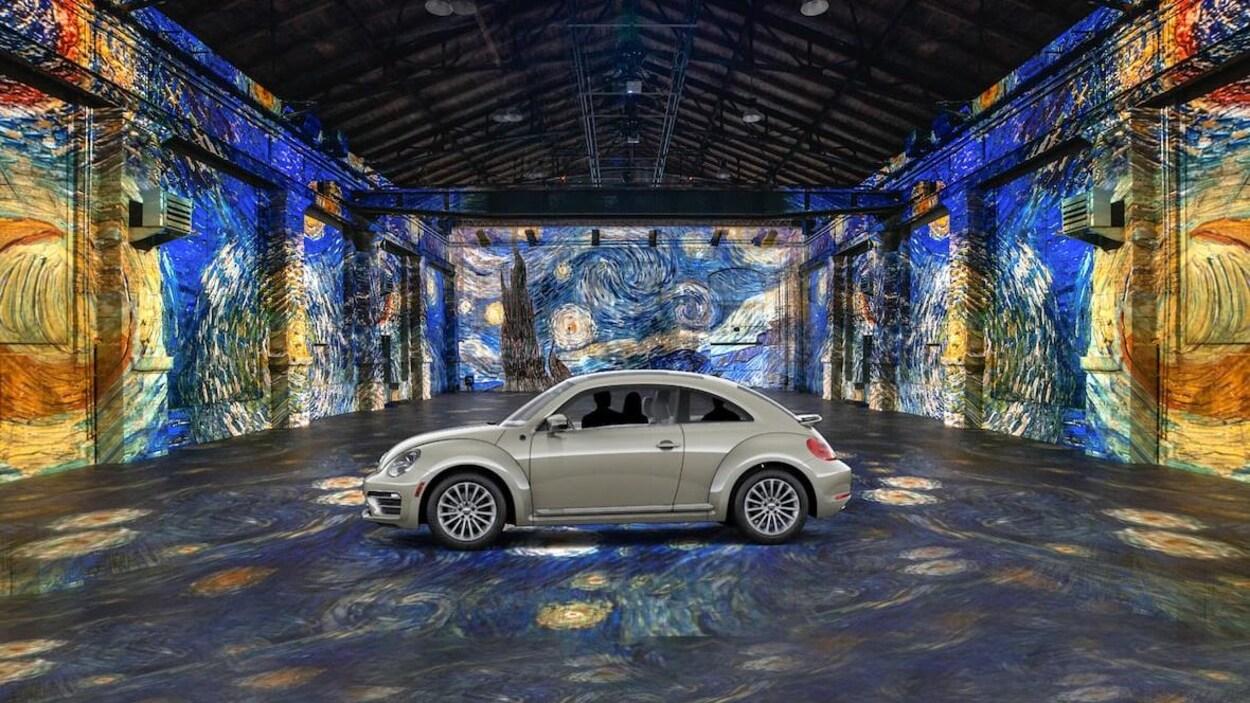 Une voiture au milieu d'un hangar désert. Des œuvres de Van Gogh sont projetées sur le sol et sur les murs.