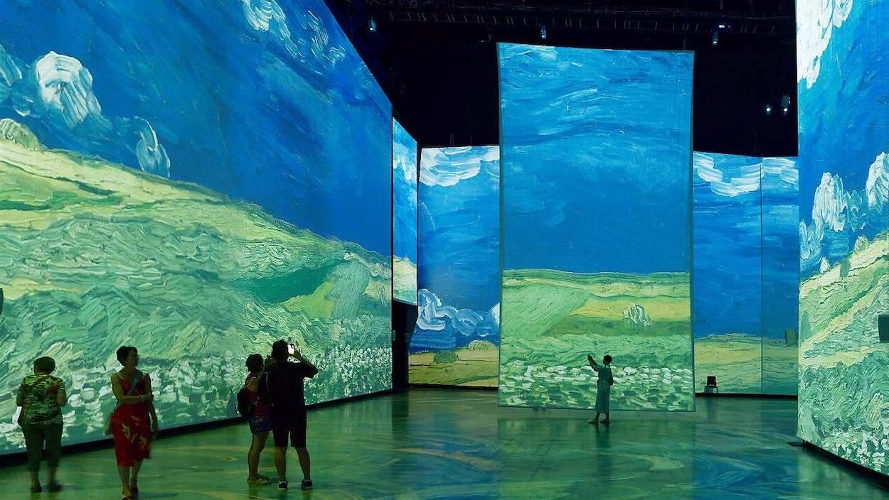 Des personnes observent des images de toiles de Van Gogh projetées sur d'immenses écrans, dans une grande salle d'exposition.