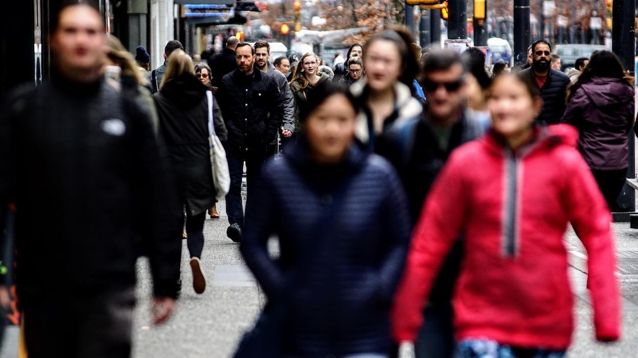 De nombreux passants marchent dans la rue Granville à Vancouver.