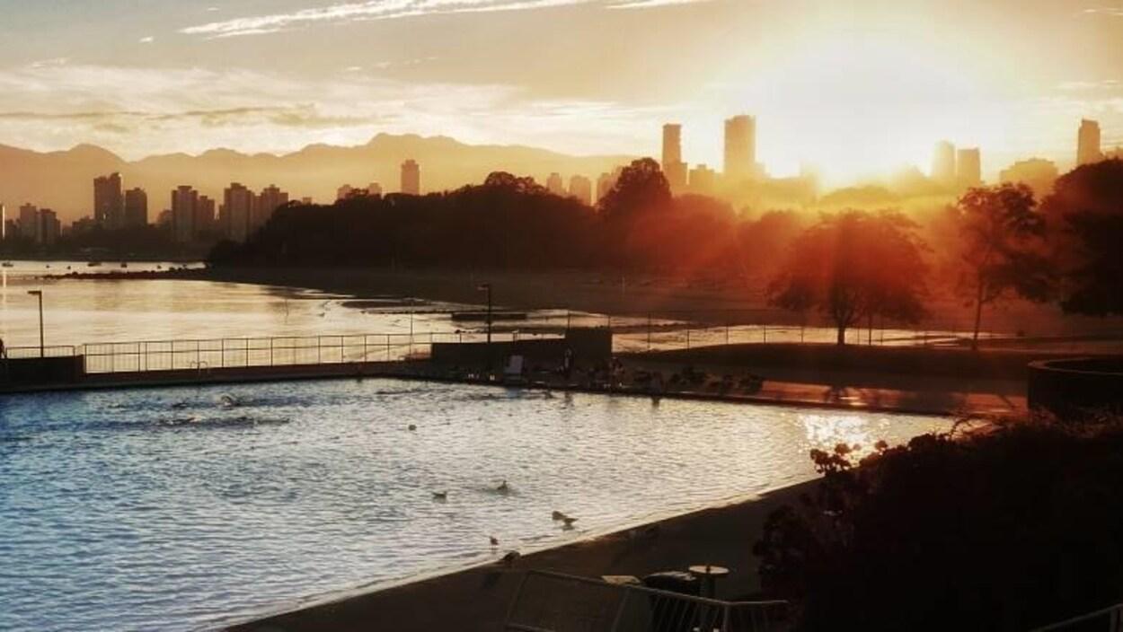 Un levé de soleil avec en avant-plan une piscine creusée et le profil du centre-ville de Vancouver.