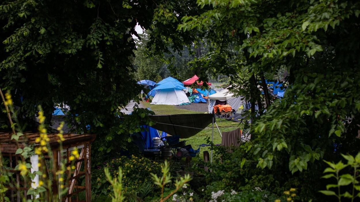 Vue des tentes du campement du parc Strathcona à Vancouver, à travers les arbres.