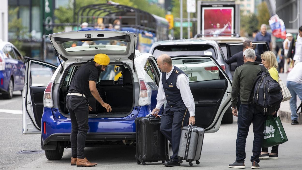 Un chauffeur de taxi empile des baggages dans le coffre arrière de sa voiture.