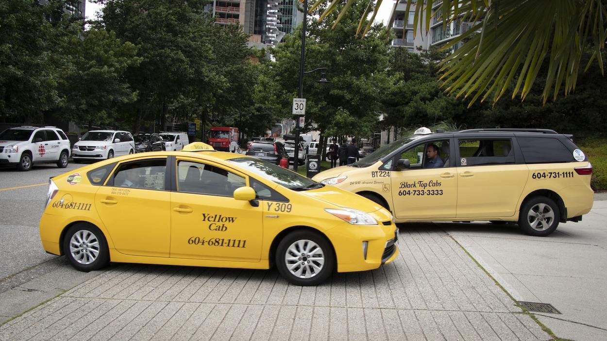 Plan large de deux voitures de taxis de compagnies différentes qui se croisent dans la rue.