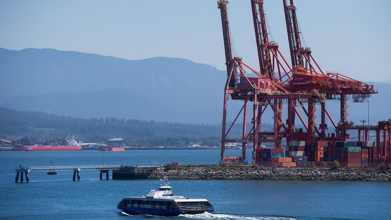 Un Seabus (bateau de transport de passagers) passe devant les installations du port de Vancouver avec des navires en arrière-plan.
