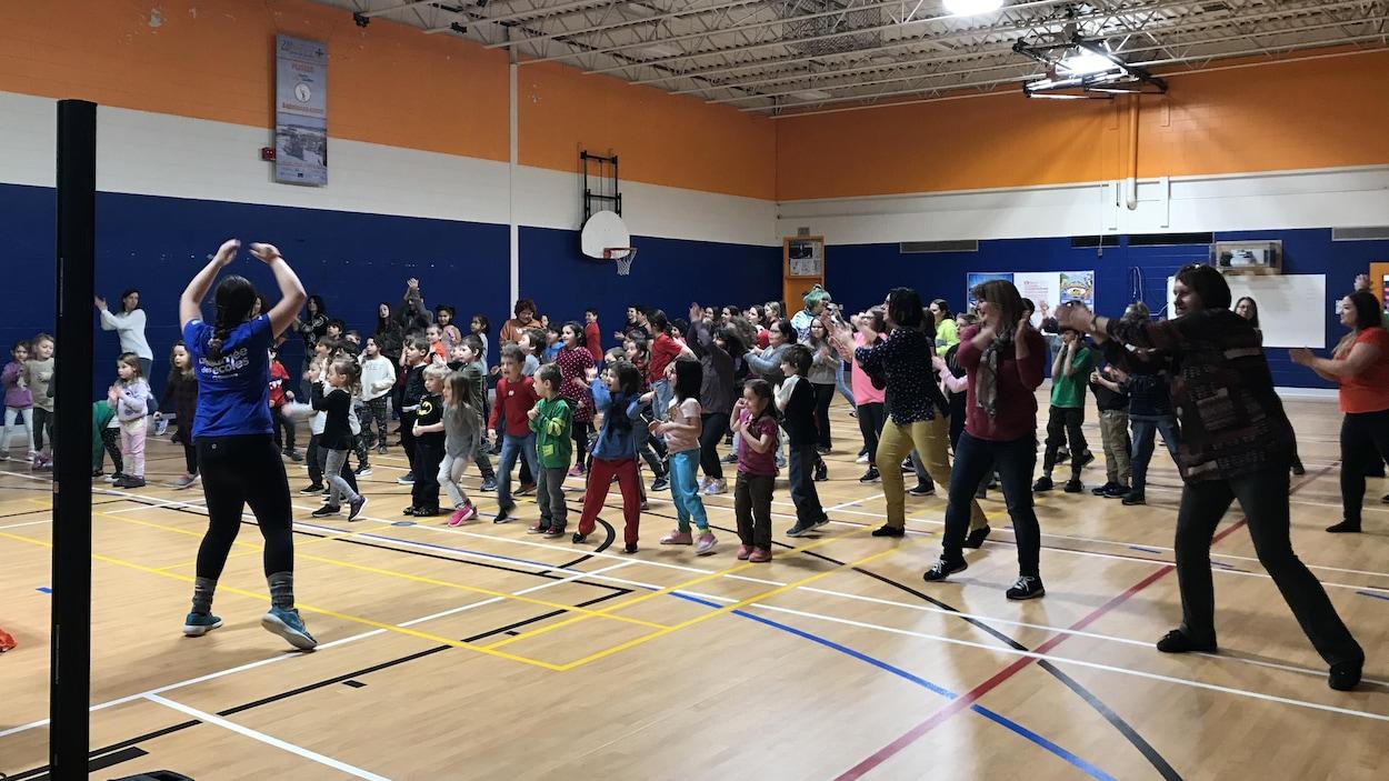 Des élèves et des adultes font des exercices dans un gymnase.