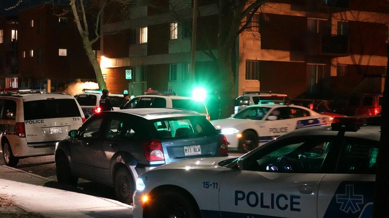Plusieurs véhicules de la police de Montréal près d'un immeuble lors d'une intervention.