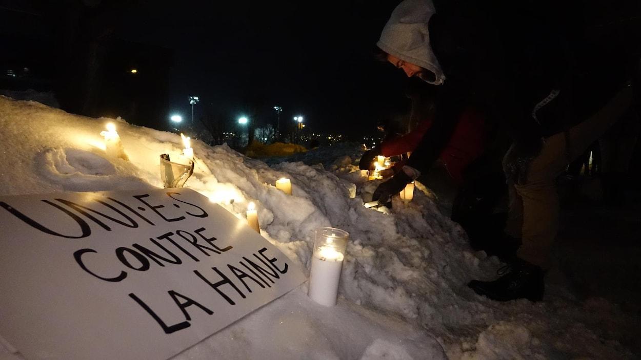 Un homme allume une chandelle lors d'une veillée à Sherbrooke en solidarité avec les victimes survenues dans une mosquée de Québec