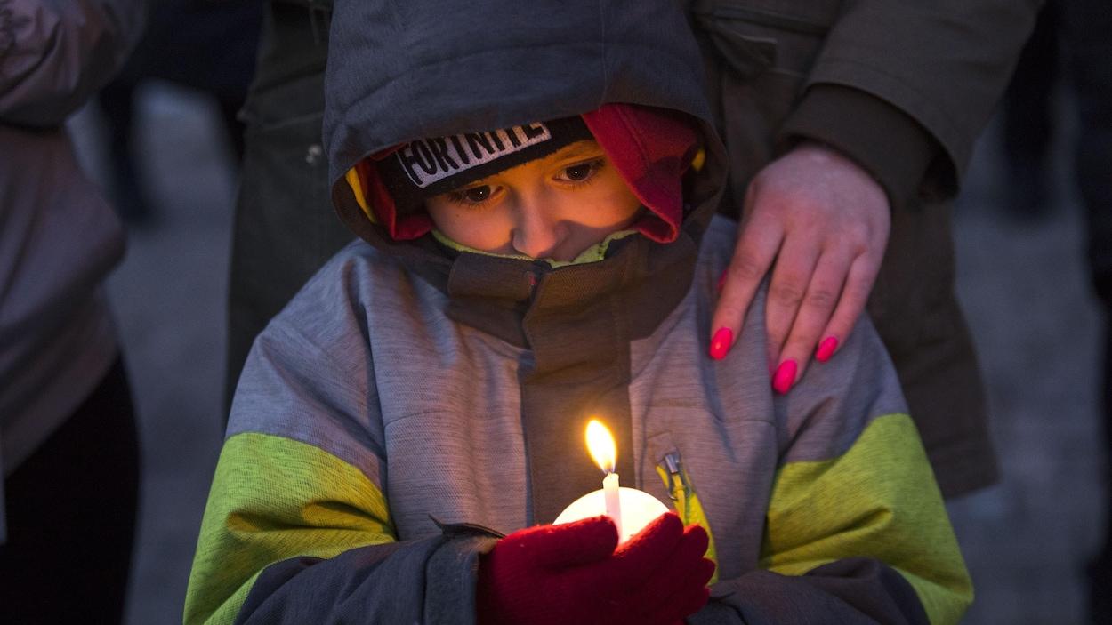 Un petit garçon tient une bougie lors d'un rassemblement.