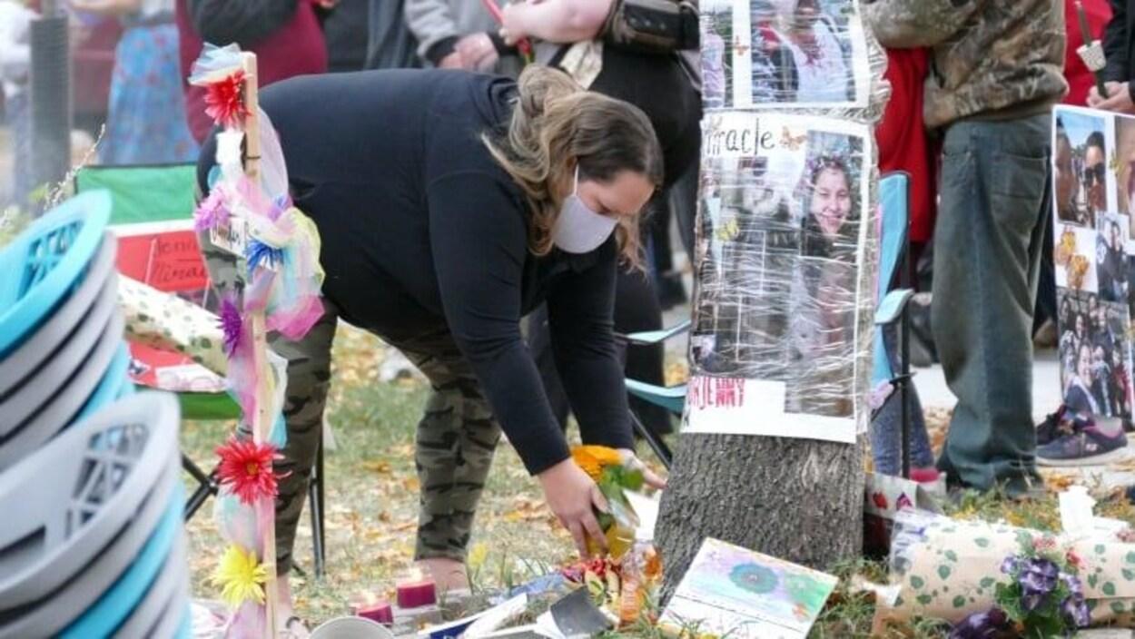 Une femme endeuillée dépose des fleurs près d'un arbre où l'on voit des photos de Jennifer Dethmers.