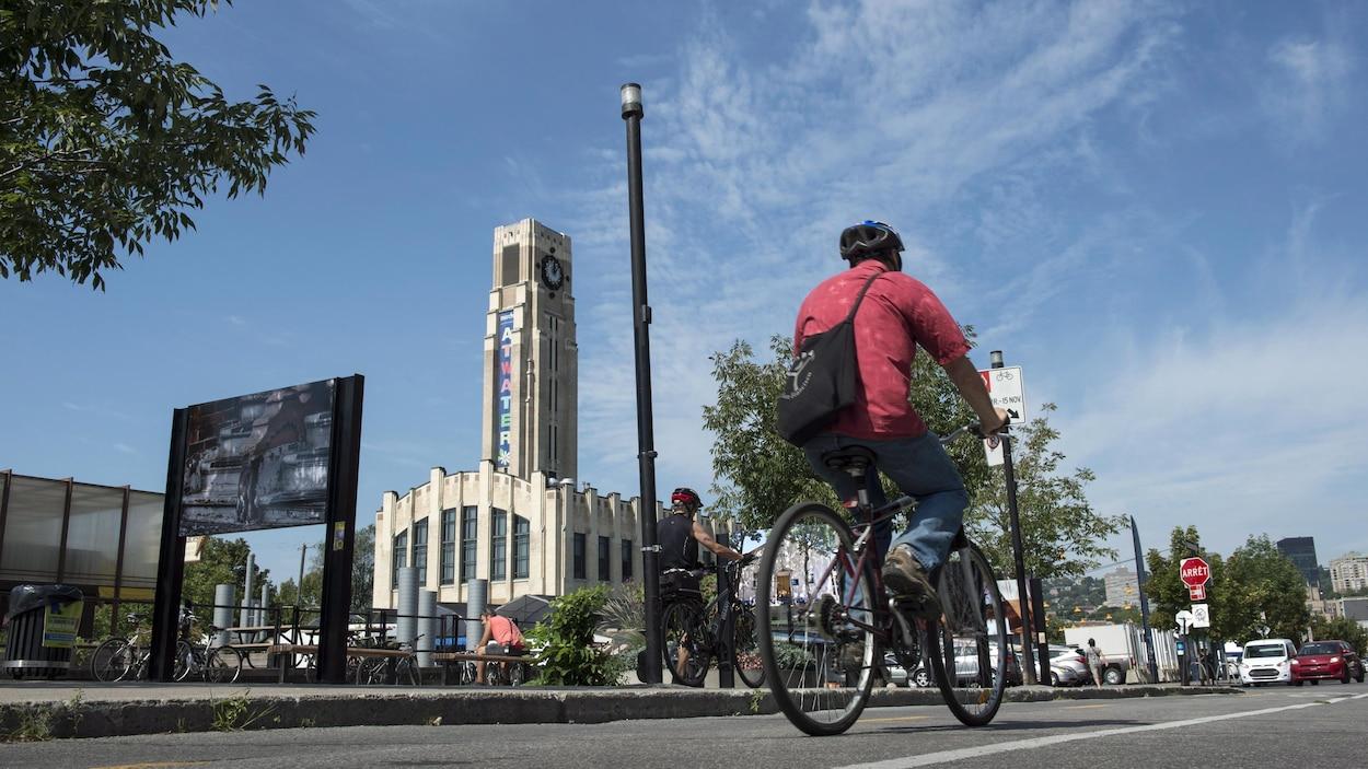 Un cycliste passe près du marché Atwater, par une belle journée d'été.