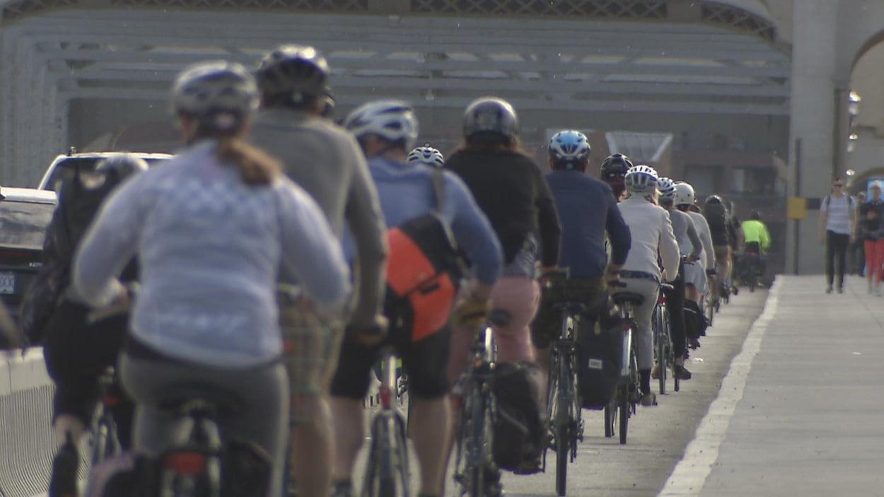 Des gens à vélo sur le pont Burrard de Vancouver un matin ensoeillé.
