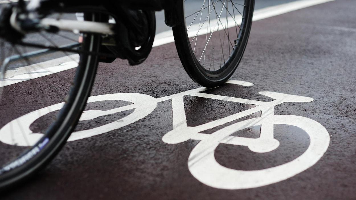 Plan rapproché d'un symbole routier de vélo peint sur la chaussée.