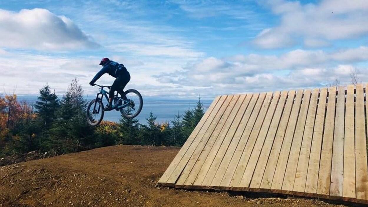 Une personne effectue un saut en vélo de montagne.