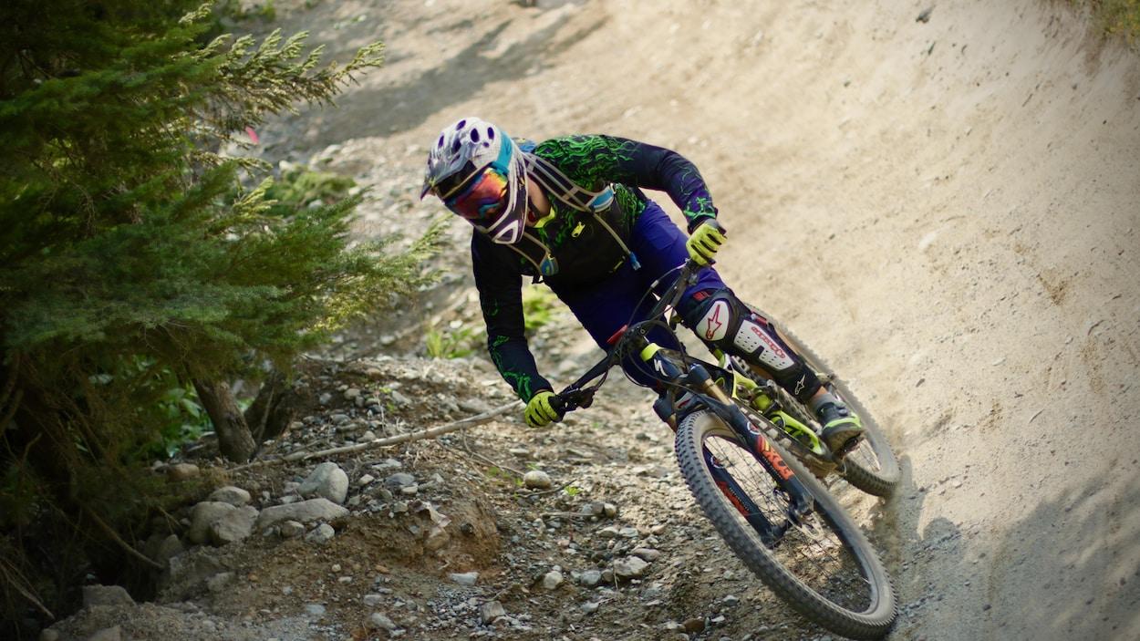 Un homme sur un vélo de montagne qui dévale une pente aménagée.