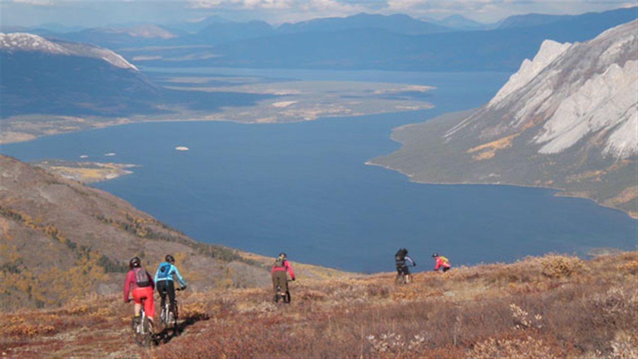 Des amateurs de vélo de montagne suivent une piste au sommet d'une montagne avec un grand lac en arrière-plan.