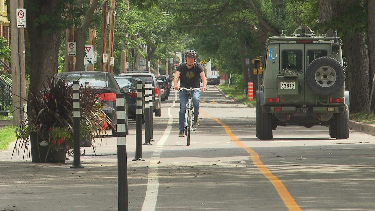 Un homme circule sur une rue alors qu'il y a une piste cyclable.