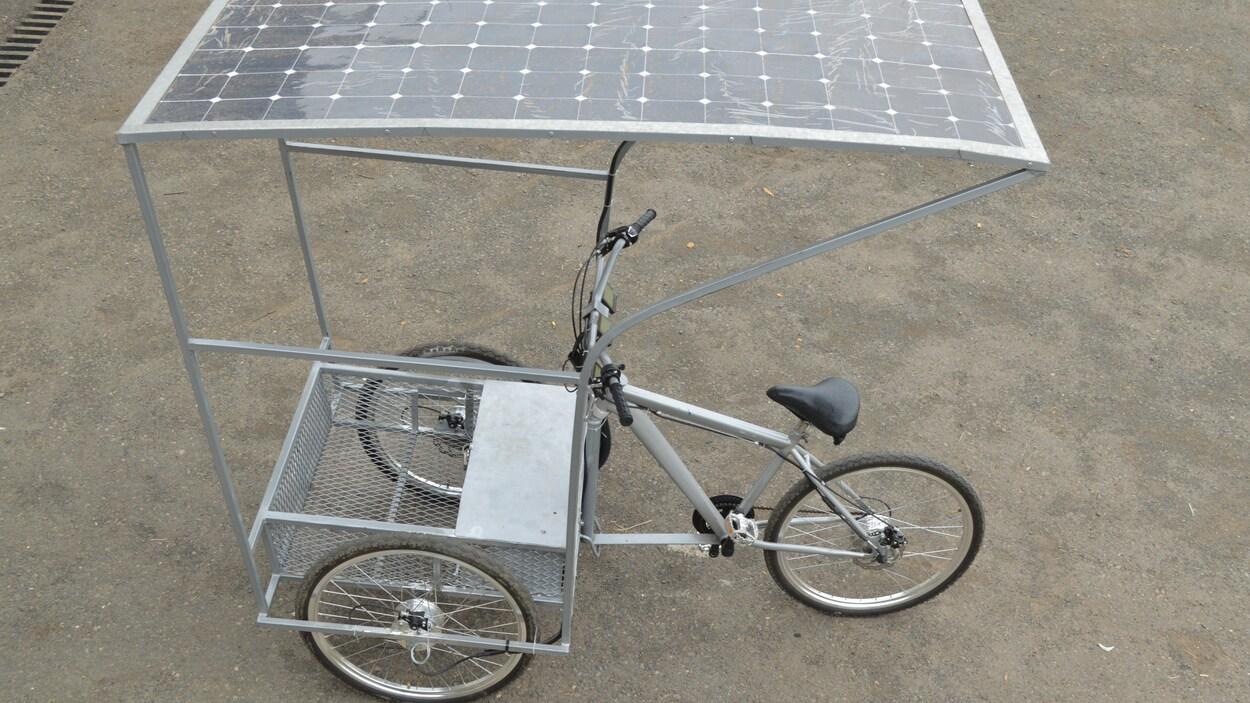 L'image montre un prototype du tricycle solaire mis au point par Solar E-cycles à même le sol.