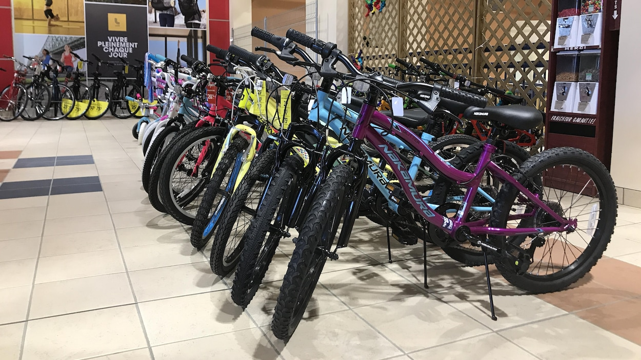 Des vélos pour enfants placés dans le couloir devant un magasin Sports Experts.