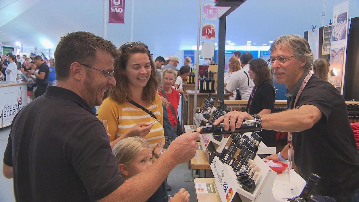 Des visiteurs s'apprêtent à déguster un produit à la Fête des vendanges Magog-Orford.