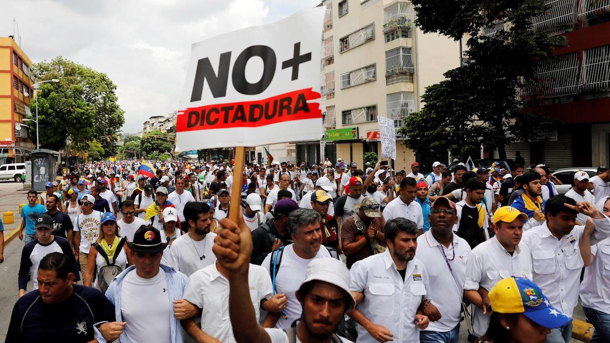 Un homme tient une pancarte « Non à la dictature » lors d'une marche qui a réuni des milliers de personnes à Caracas, au Venezuela.