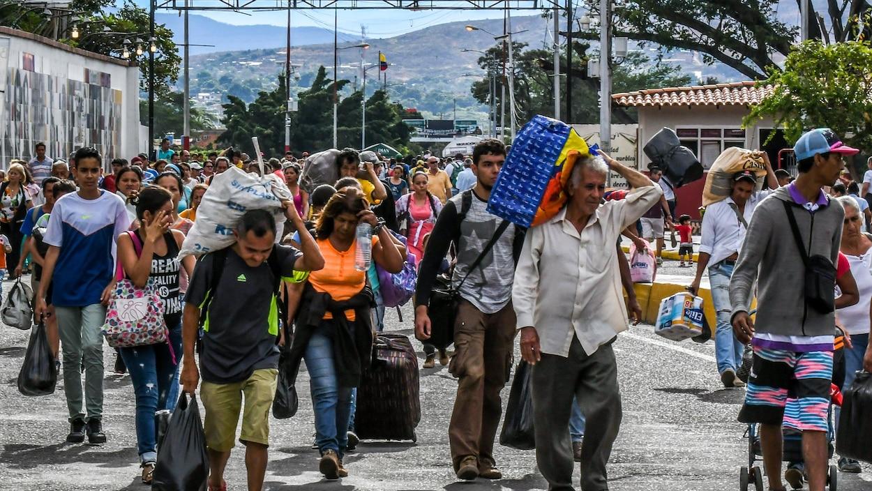 Des gens marchent en traînant des valises.
