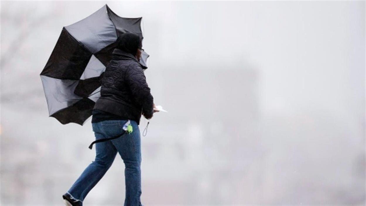 Une femme avec un parapluie retourné par le vent