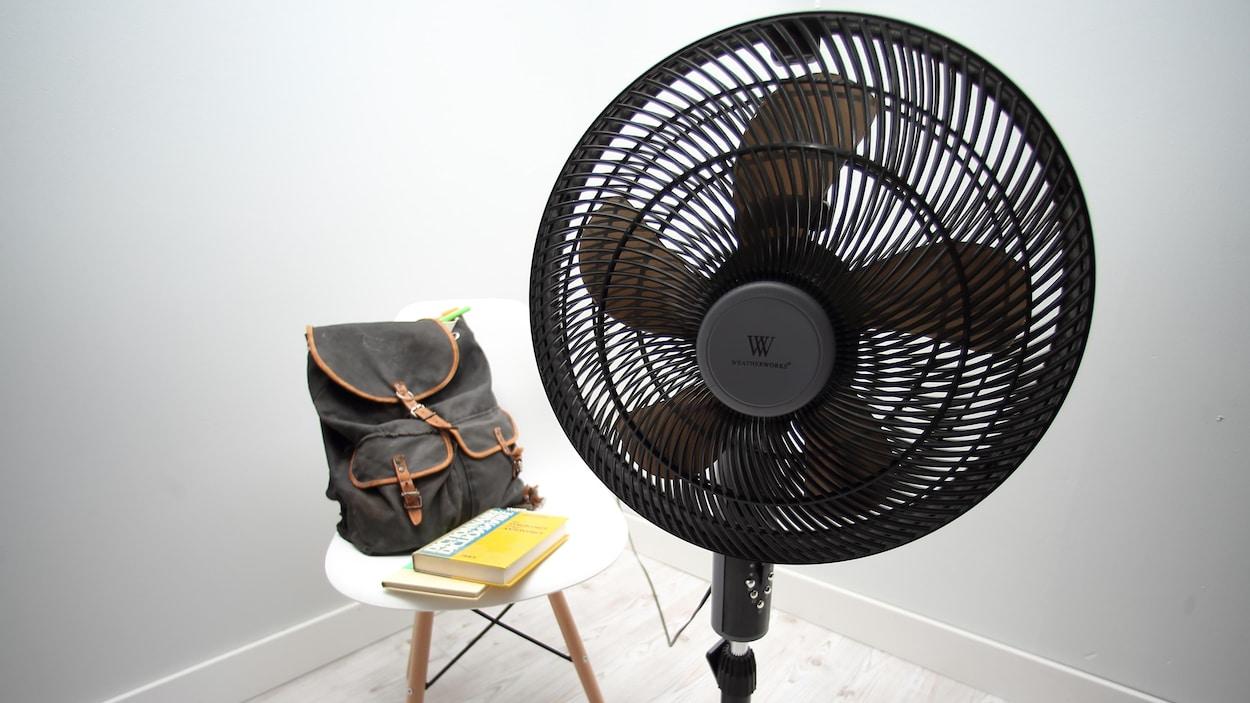 Un ventilateurs avec deux livres et un sac à dos en arrière plan.