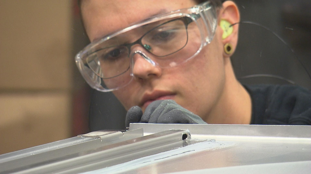 Une femme qui porte des lunettes protectrices inspecte une feuille de métal dans une usine.