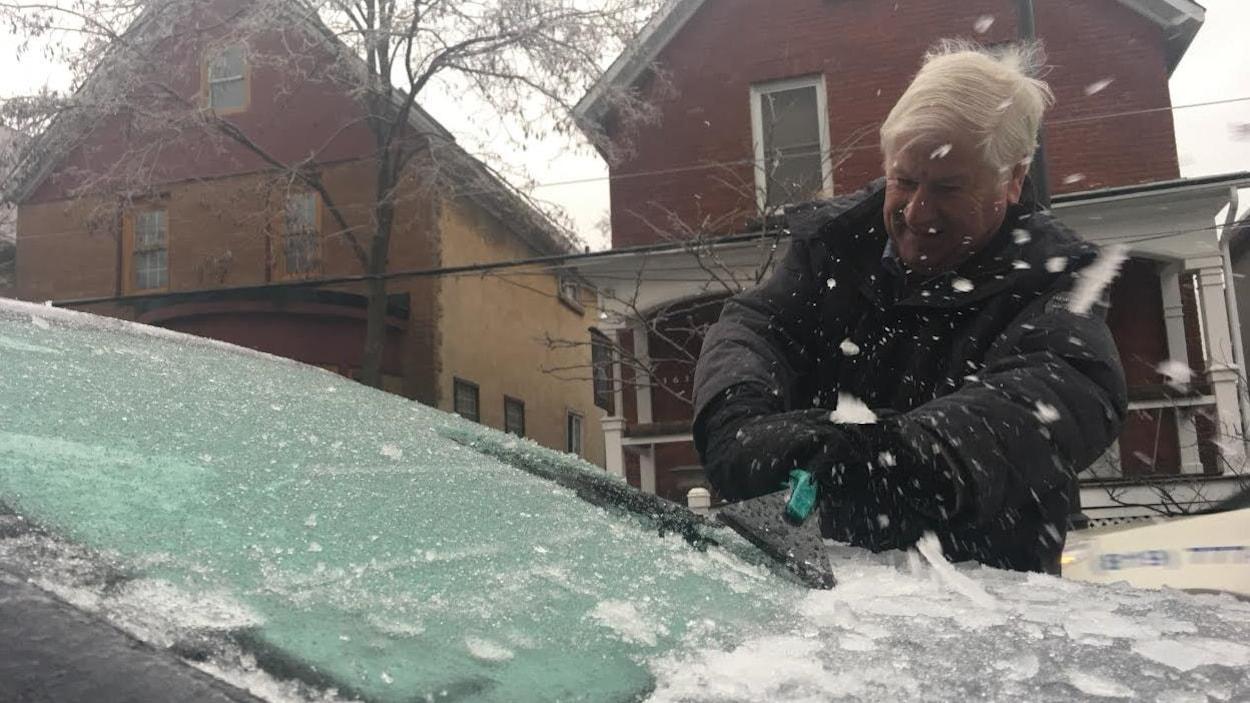 Un homme racle le pare-brise de sa voiture à Ottawa.