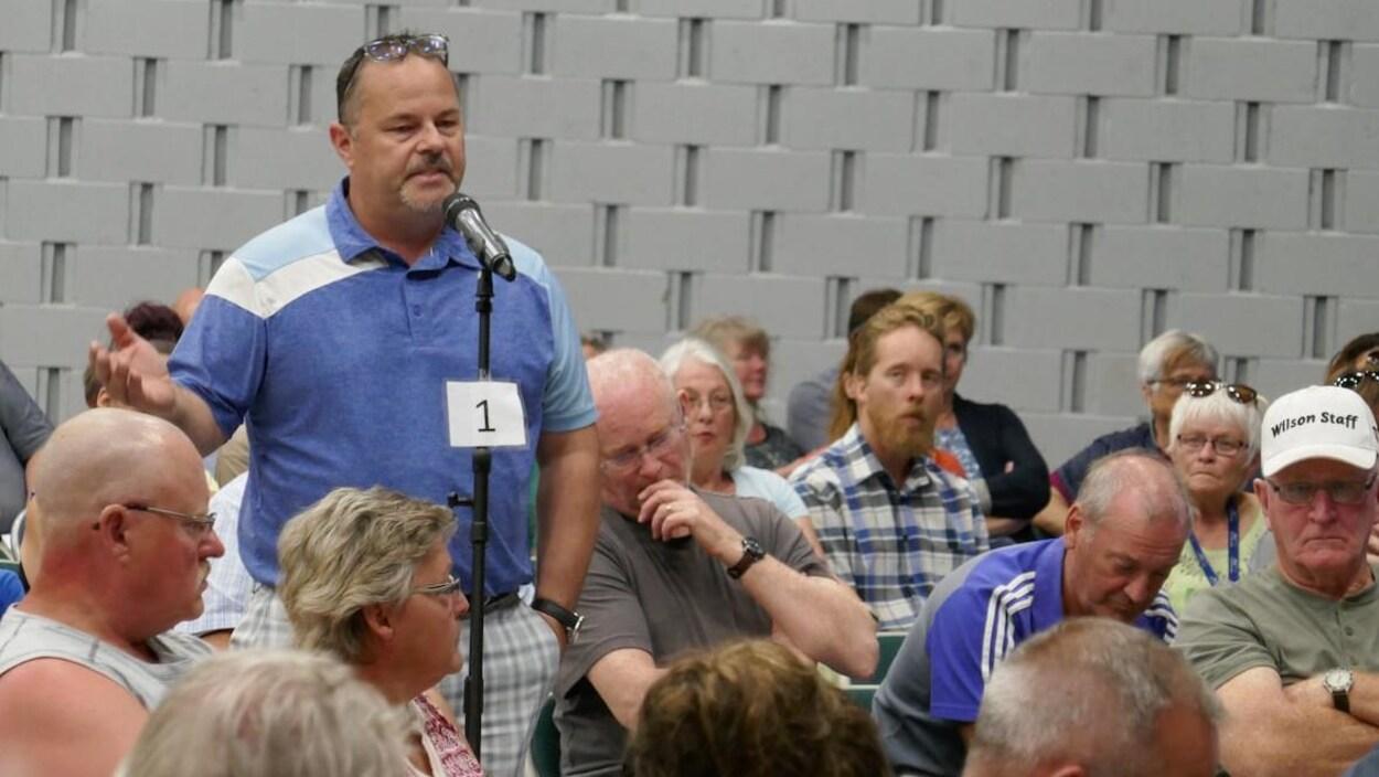 Un homme s'adresse à une foule assise dans une grande salle.